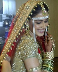 Genelia's bridal saree is a red traditional saree with a Golden blouse.