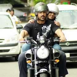 John Abraham riding his Yamaha VMax on Mumbai's roads. A Radio Jockey is riding pillion with him.