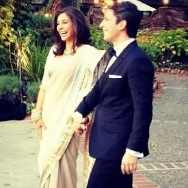 Photo of Lisa Ray in her wedding sari, holding hands with husband Jason Dehni.