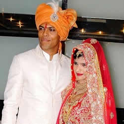 Wedding picture of Bowler Umesh Yadav in a Sherwani and wife, Tanya, in a red Bridal Chagra Choli.